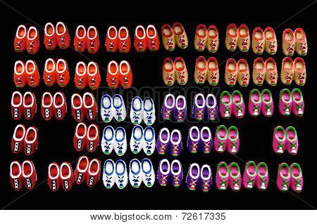 Small Dutch wooden shoes against a black background