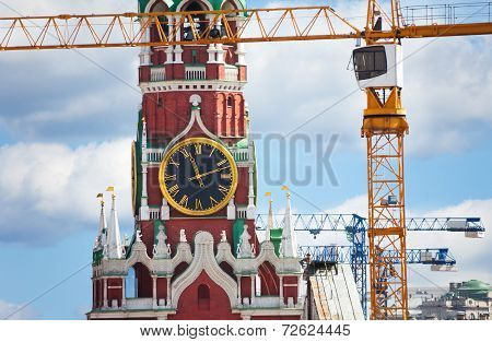 Kremlin clock up view with construction cranes