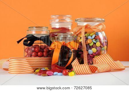 Candy In Glass Jars With Orange And White Stripe Ribbon For Halloween Or Party Favors.