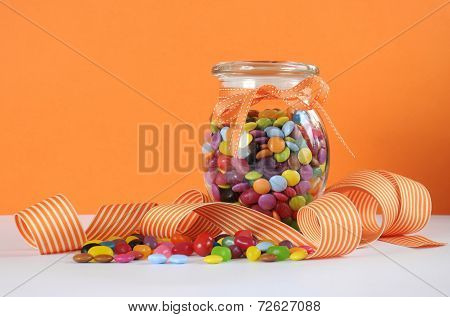 Candy In Glass Jar With Orange And White Stripe Ribbon For Halloween Or Party Favors.