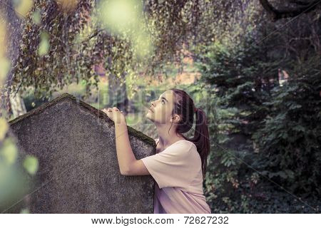 Vintage Shoot Of A Woman Touching A Moss Overgrown Tombstone