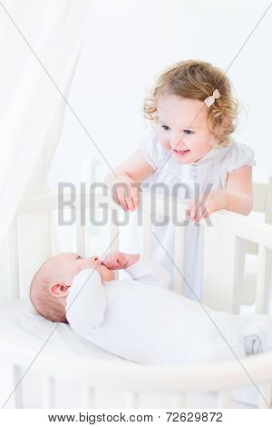Adorable Curly Toddler Girl In White Dress Talking To Her Newborn Baby Brother In A White Round Crib