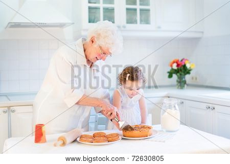 Loving Grandmother Baking An Apple Pie With Her Adorable Toddler Granddaughter In White Kitchen