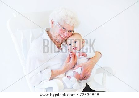 Beautiful Grandmother Singing To Her Newborn Baby Grandson Sitting In A White Rocking Chair