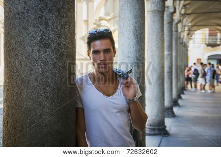 Handsome Young Man Standing Outdoors Under Colonnade