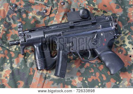 modern 9 mm submachine gun on camouflaged background