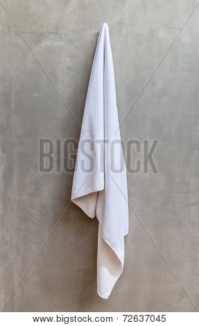 Hanging White Towel Draped On Exposed Concrete Wall In The Bathroom