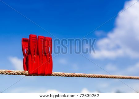 Three Red Plastic Clothespins Hang On A Laundry Line And Bright Blue Sky.