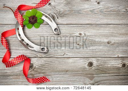 Horseshoe, Shamrock And Red Ribbon On Old Wooden