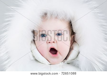 Cute Yawning Baby Girl Wearing A Huge White Fur Hat And A Warm White Winter Snow Suit