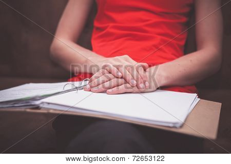 Woman Sitting On Sofa With Documents