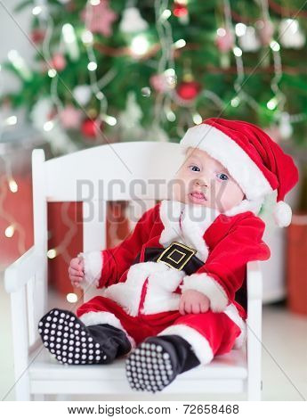 Funny Newborn Baby Boy In A Santa Outfit Sitting Under A Decorated Christmas Tree