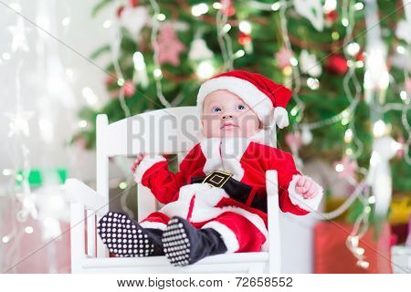 Little Newborn Baby Boy In Santa Outfit Sitting Under A Christmas Tree
