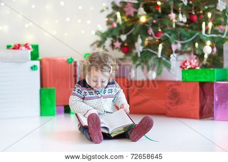 Little Happy Toddler Girl With Curly Hair Reading A Book Under Beautiful Christmas Tree