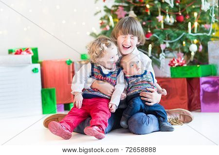 Three Happy Children under a beautiful Christmas tree