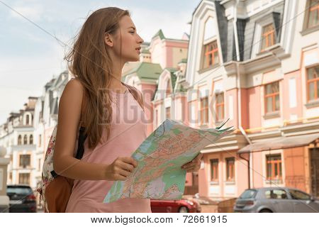 Waist-up portrait of pretty female traveler on the street holdin