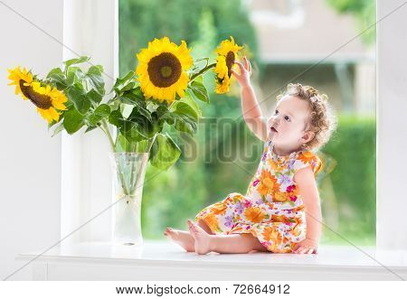 Happy smiling baby girl playing with beautiful sunflowers on a sunny summer day sitting at a window