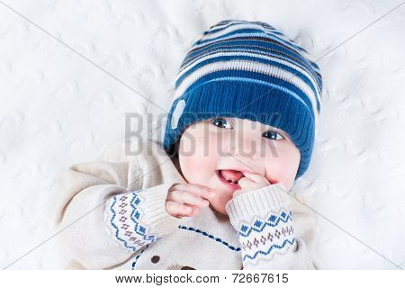 Funny Laughing Baby In A Blue Knitted Hat And A Warm Sweater