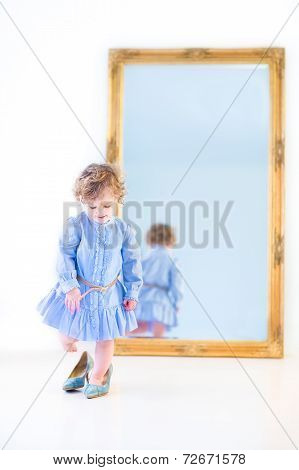 Funny Toddler Girl In A Blue Dress Trying On Her Mother's High Heels Shoes In Front Of A Big Mirror