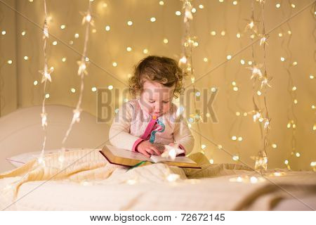 Cute Little Toddler Girl Reading A Book In A Dark Room With Christmas Lights