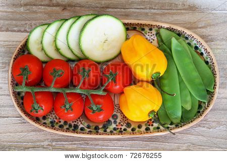Cherry tomatoes, courgette, sugar snaps and adjuma peppers on plate on wooden surface