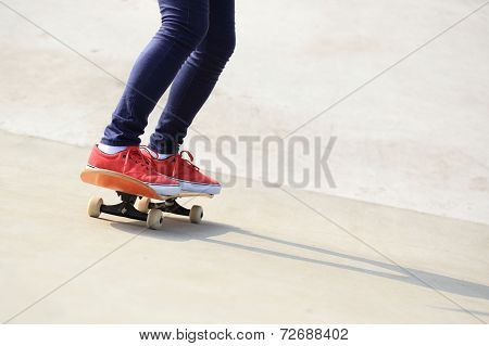 woman legs skateboarding at skatepark ramp