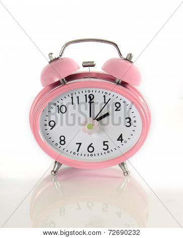 Daylight Savings Time Pink Clock On Reflective Glass Concept Against A White Background.