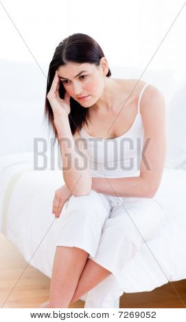 Portrait Of A Unhappy Woman Sitting On Bed