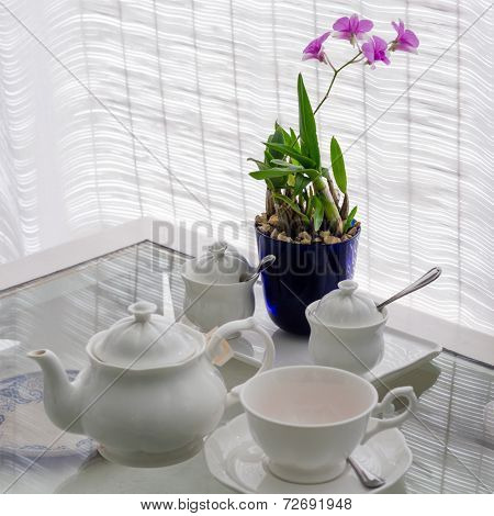 Ceramic Utensils On Table With Flower Decoration