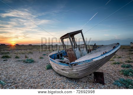 An Old Abandoned Wooden Fishing Boat With Nets Washed Up On A Shingle Beach