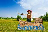 foto of pirate sword  - Pirate girl with black hat stands on ship made of cardboard and holds sword up in the field - JPG