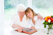 stock photo of grandma  - Beautiful Woman And Her Loving Mother Watching Together A Black And White Photo Album - JPG