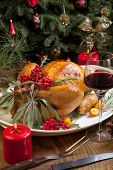 picture of turkey dinner  - Roasted turkey garnished with sage rosemary and red berries in a tray prepared for Christmas dinner - JPG