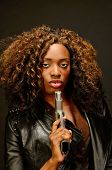 pic of gangsta  - A young african american female holds a semi automatic pistol during this photo shoot against black - JPG