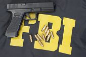 picture of ammo  - 9mm handgun with ammo on FBI uniform - JPG