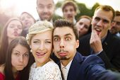 stock photo of dress-making  - Young couple of newlyweds with group of their firends taking selfie and making funny grimaces - JPG