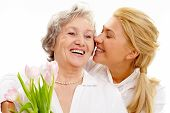 stock photo of mother daughter  - Portrait of pretty woman kissing and embracing her mother during holiday - JPG