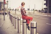 foto of bollard  - A young woman is sitting on a bollard by the roadside in the city - JPG