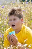 foto of rhinitis  - Boy with allergic rhinitis in the meadow - JPG