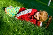 The Small Beautiful Girl Sits On A Green Lawn And Laughs