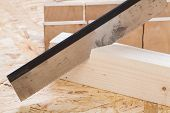 pic of joinery  - Toothed steel hand saw cutting through a new beam of wood left in position surrounded by wood chips with nobody in the frame in a DIY carpentry woodworking or joinery concept - JPG