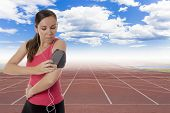 picture of bangles  - young female runner ready to run with earphones on and playing music from the mobile phone in a bangle on a running track background - JPG