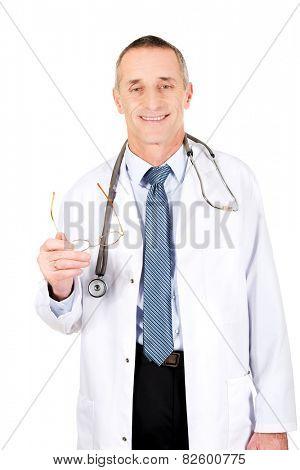 Smiling mature male doctor holding his eyewear.
