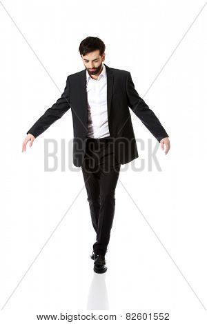 Businessman walking carefully, try to balance himself.
