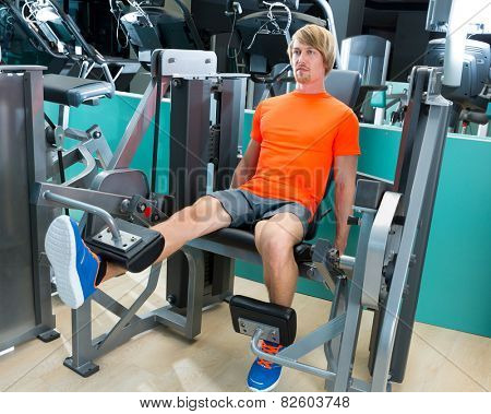 Gym blond man leg extension quadriceps exercise workout at indoor