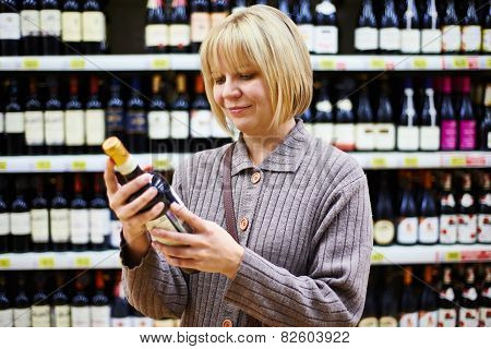 Woman Reading Label On Bottle Of Wine In Store