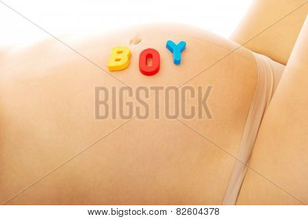 Belly of a young pregnant woman with boy lettering