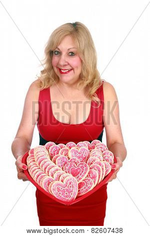 a lady holds a big heart shaped tray of valentine day heart shaped cookies. isolated on white with room for your text