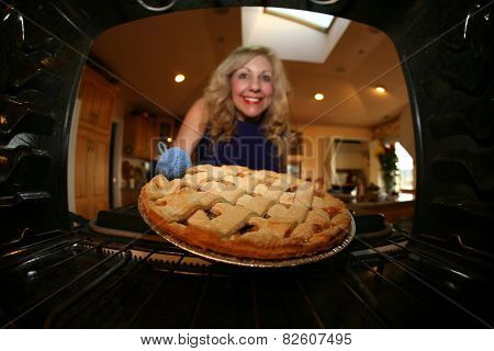 Sweet retro grandmother holding a freshly baked lattice top apple pie. Shot from Inside the Stove for a unique view not often seen. Apple Pies and Grandmothers go hand in hand and are Very American.