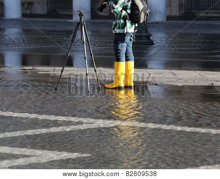 Photographer With Yellow Boots At High Tide In Venice